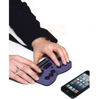 Hands operating the Braille keyboard device beneath a cell phone