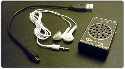 A medium-sized black device with a built-in speaker, roughly the size of a smartphone. Next to it are white earbuds and a USB cord.