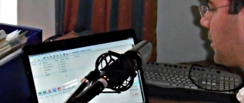 A man speaking into a microphone and looking at a laptop.