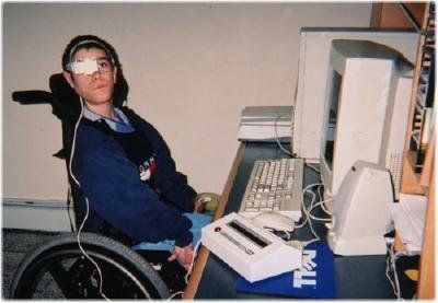 A man with one eye closed sitting on a wheelchair infront of a computer using VisionKey