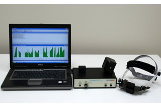 A black, open laptop shown next to two black medical devices. The laptop is displaying a green histogram.