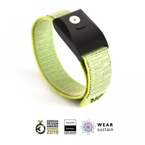 Wristwatch-sized device with a light green band connected to a black rectangular device with a small black button and a small round silver button.