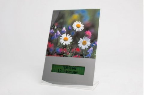 An image of white, purple, and pink flowers above a digital display featuring the day of the week, month, and date.