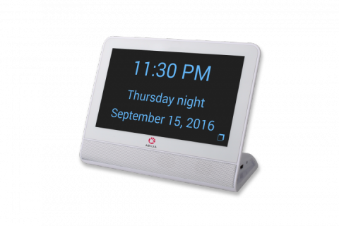 A white rectangular device with a black background and large blue text displaying the time, day, time of day, and date.