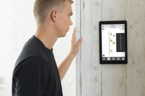 A tablet featuring the MEMOplanner screen hung on a wall.