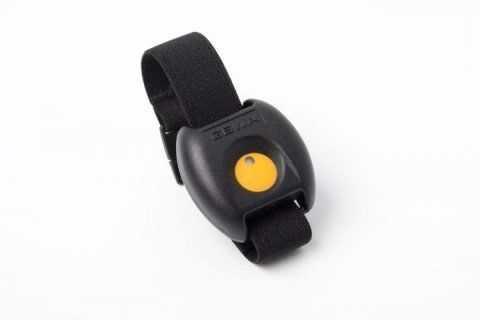 A small black rectangular device attached to a wristband with a yellow button in the middle.