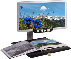 Widescreen, flat-panel LED display with a picture of a field on it attached to a desktop stand with an open book on it.