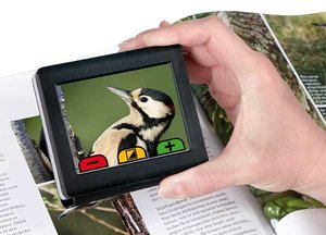Picture of a hand holding a small video screen, which is being held over a book and shows a magnified image of a bird.