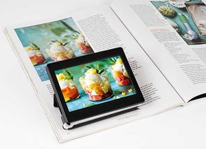 Picture of a small rectangular video screen sitting, using a stand, on an open book, with an image from the book magnified on the screen.