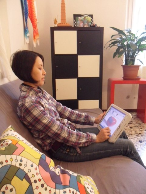 Picture of a woman sitting on a couch holding a tablet PC on her lap with her left hand and pointing to the screen with her right hand.