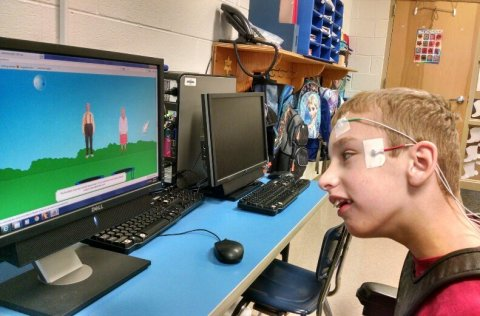 The side-view of a young boy sitting in front of a computer with a colorful screen image of people standing in the grass. The user has electrodes on his temple and forehead.