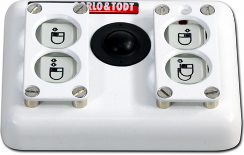 A small rectangular device with 4 buttons in a 1x2 layout on either side of a small, centered trackball. A mouse or double mouse is drawn on the buttons and a right or left click highlighted. Above the buttons on the right side is a led light indicator. This housing also showcases a raised finger-guard over the four buttons with each corner of the guard screwed to the housing.