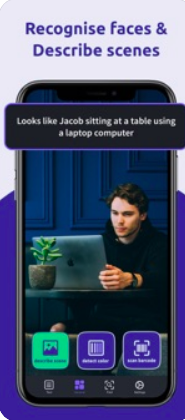 "A smartphone's screen featuring a male seated at a table using a laptop. The tagline says, ""Recognize faces and describe scenes"". The label on the phone reveals what's in the picture: Looks like Jacob sitting at a table using a laptop computer."