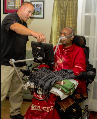 A wheelchair user with a technician indicating something on the display screen is shown. The display screen is mounted on the wheelchair with articulating arms.
