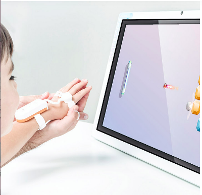 A partial shot of a small child viewing a screen. The child's arm is extended and the hand is supported in a larger person's hand. On the back of the wrist and knuckles are straps and a white rectangular device.