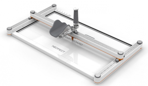 A frame-type device with a center bar resting on and stretched across the width of a rectangle that is placed on a table. The center bar has a u-shaped attachment and an upright handle in its middle position.
