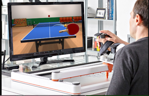 A sideview of a man watching a screen with a virtual ping pong game on it. The man has his wrist supported and strapped in a medical device with his hand clutching an upright handle. There is another person's hand touching the handle also.