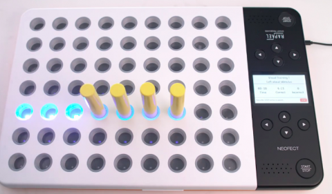 """A 9x7 grid of peg holes in a whiteboard that has a cord attached on the upper right side. Seven of the holes have a neon blue light that is on, and 4 of those holes have long yellow pegs in them. The right side of the board has a narrow strip which is black and has two sets of buttons, each set for a person sitting on either side of the board. These buttons are labeled with directional arrows. There is also a speaker on both sides, and a button in each of the two corners labeled """"start/stop""""."""