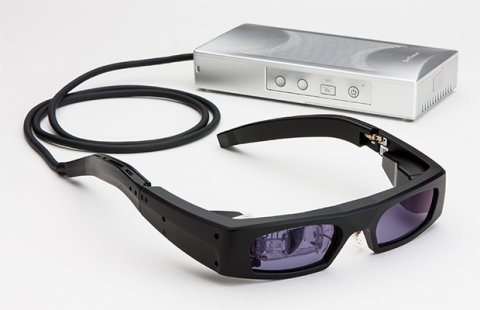 Black glasses with dark tinted lenses and a cord protruding from the end of the stem that leads to a small rectangular device with menu options on the side.
