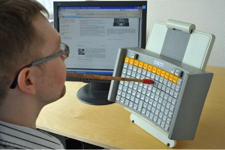 The keyboard attached to a stand being used with a mouth stick.