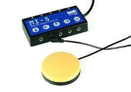 Small, rectangular black wired interface with one yellow switch attached to one of its 5 ports.