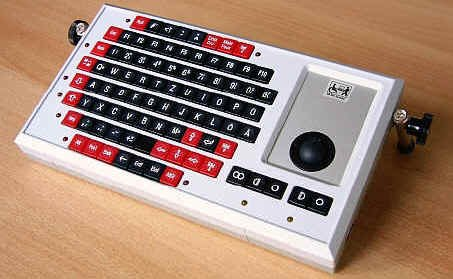 Wired, rectangular keyboard with legs and trackball on right.