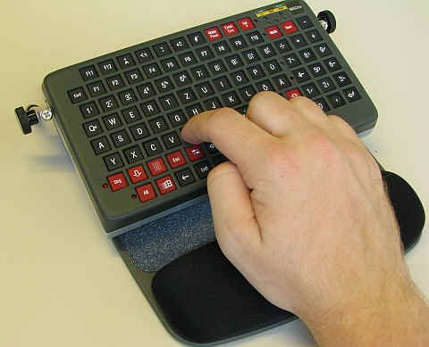 Small rectangular keyboard with hand on palm rest pushing the keys.