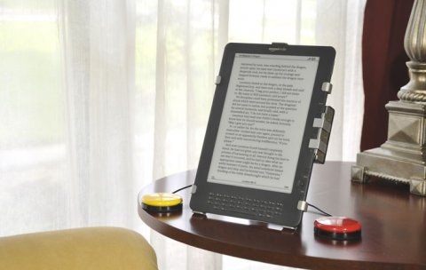 Amazon Kindle fitted with PageBot standing on a desk with two switch buttons attached.