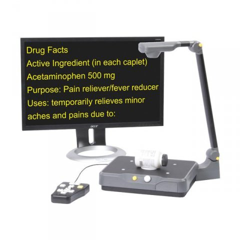 A stand magnifier with a camera at the top, and beneath, a platform base for placing materials on. Next to it, a large monitor is displaying content in high-contrast, yellow-on-black font.