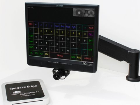 A small, square device next to a desktop screen with a camera at its base on an adjustable, vertical mount.