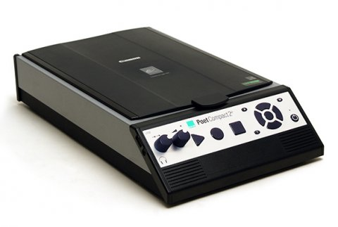 A black rectangular device with silver sides and front. Menu options on the sloped front panel are accessed via two raised dials on the left side and 3 large buttons: a triangle, circle, and a square, in the middle of the front panel. A speaker is also there on the right side of the front panel.