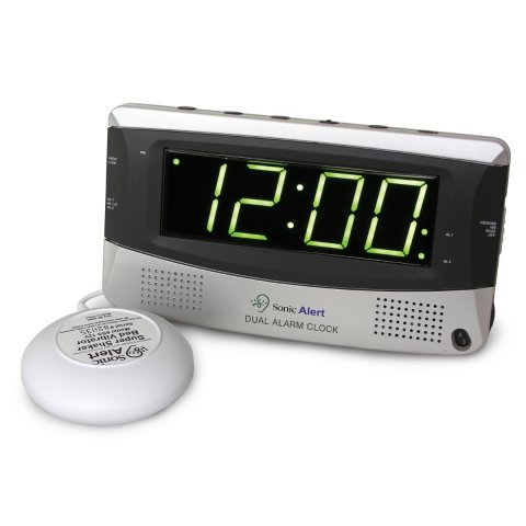 A rectangular, silver, alarm clock with large led display and two speakers on either bottom side of the front face; control buttons on the top face; and, a small, wired, domed shaker device to the alarm clock.