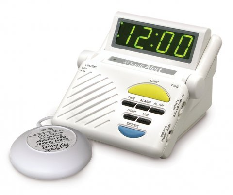 White device with digital clock, control buttons, speaker, and display.  A round white device attached by wire to the main unit.