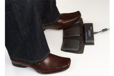A foot is shown a black foot pedal (one of three).