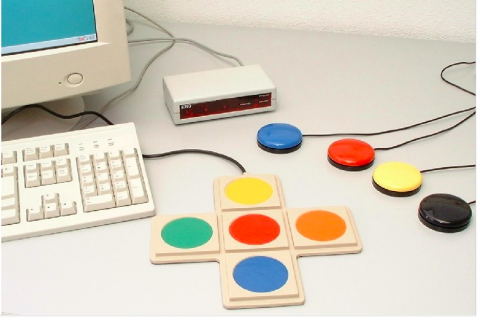A computer screen and keyboard alongside a white console and several adapted switches.