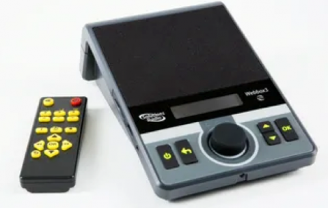 A rectangular and slanted control box divided into a black speaker on the upper half and a lower grey panel with 5 large keys and a dial. Next to this box is a black remote with bright yellow keys and a red power button.