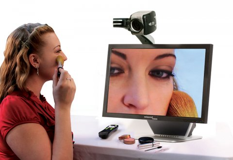 A woman is applying makeup and using the magnifier as a mirror, with the monitor displaying a zoomed-in video feed of her face.