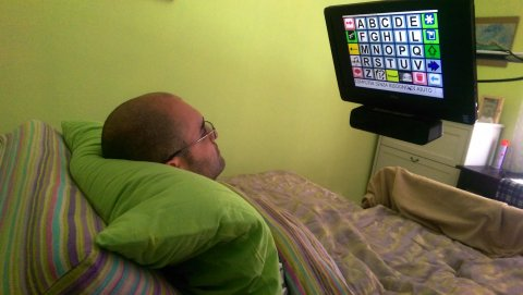 A man lying in bed controlling CiaoMundo with his eye movement. A monitor is positioned on a tall stand over his bed so the user can look at it comfortably.