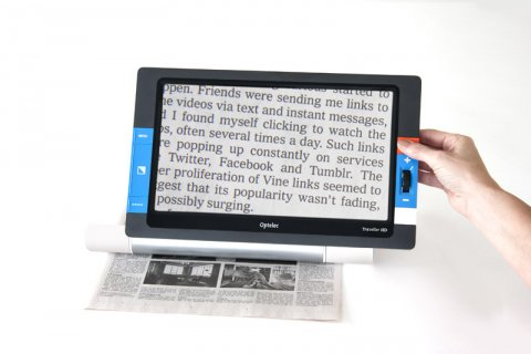 Rectangular tablet with blue control buttons along the edges. A hand holding the tablet above a newspaper and a digital version of a magnified newspaper excerpt displayed on screen.
