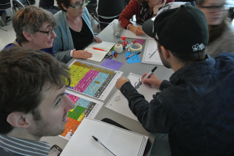 Volunteers sitting around a table and creating AAC grids on paper.
