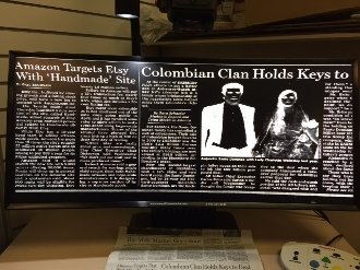 Large curved flat screen monitor, displaying a magnified newspaper page in high contrast white-on-black.