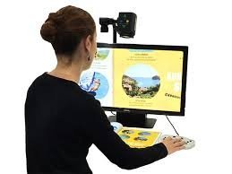 A woman sits in front of a monitor with a magnifier mounted at the top with controls to zoom and a light attached.
