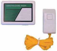 Small rectangular speaker output device on left and small, white handheld device with one button on right, attached to a yellow cord.