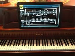 Image of Lime Lighter Leggiero model mounted on the music rack of a piano and displaying magnified music as white notes on a black background on a grand staff.