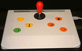 Large white rectangular device with joystick in center and three colored buttons on either side.