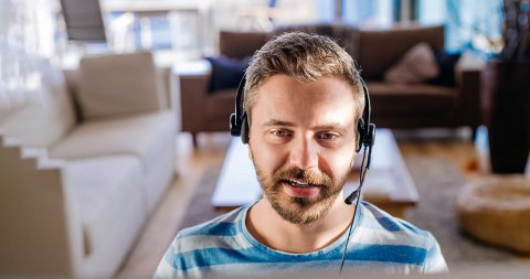 The torso view of a man facing forward wearing a headset and a living room behind him.