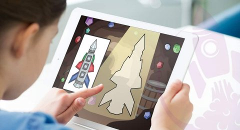 Child holding a tablet computer and pointing at an image of a rocket ship on the screen.