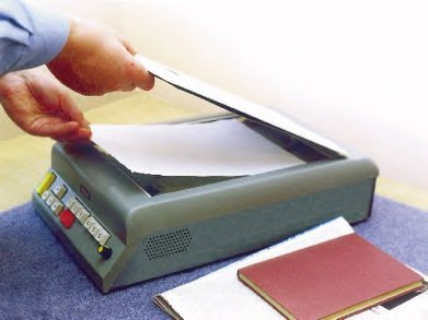 A medium-sized grey device resembling a scanner. A user is lifting the top and placing a sheet of paper on the scanning bed.