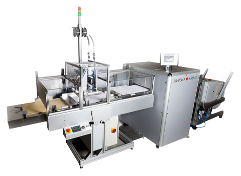 Large, white printing press with a long tray at the end for rapidly dispensing bulk printed materials. This model also includes an automated book binding system.
