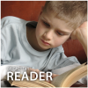 Picture of a boy in a white shirt reading a book with his left elbow on a surface and his left hand holding up his head. With hisright hand, he holds the book open.